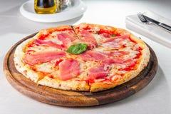 Geschmackvolle ganze italienische Pizza überstieg mit dünn geschnittenem Prosciuttoschinken Selektiver Fokus Stockfotografie