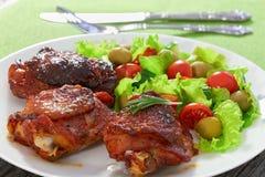 Geschmackvolle gegrillte Hühnerschenkel mit grünem frischem Salat Stockfotografie