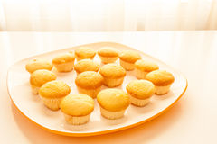 Geschmackvolle gelbe Muffins in einer weißen Platte Stockfotos