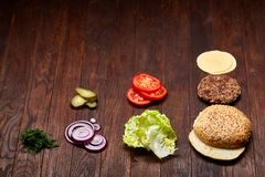 Geschmackvolle Hamburgerbestandteile werden separat von oben, schön harmonisch, Nahaufnahme, Draufsicht ausgebreitet stockfotografie