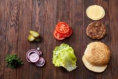 Geschmackvolle Hamburgerbestandteile werden separat von oben, schön harmonisch, Nahaufnahme, Draufsicht ausgebreitet lizenzfreie stockbilder
