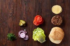 Geschmackvolle Hamburgerbestandteile werden separat von oben, schön harmonisch, Nahaufnahme, Draufsicht ausgebreitet stockbilder
