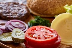 Geschmackvolle Hamburgerbestandteile werden separat von oben, schön harmonisch, Nahaufnahme, Draufsicht ausgebreitet lizenzfreies stockbild