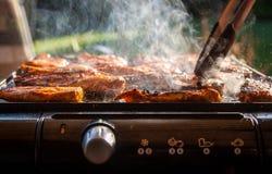 Geschmackvolle Hühnersteaks auf dem elektrischen Grill des Kontaktes Stockbilder