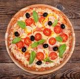 Geschmackvolle köstliche Pizza auf den alten Brettern Stockbild