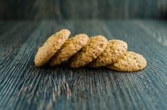 Geschmackvolle Kekse auf Getreide auf hölzernem Hintergrund Stockfotografie