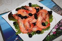 Geschmackvolle Lebensmittelgarnelen mit Oliven auf Platte Lizenzfreies Stockbild