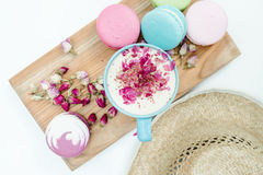 Geschmackvolle macaron Plätzchen mit einer blauen Schale Cappuccino und Strohhut auf weißer Tabelle Lizenzfreies Stockfoto