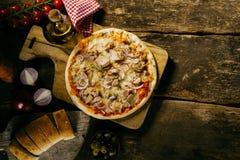 Geschmackvolle Meeresfrüchtethunfischpizza in einer rustikalen Küche Lizenzfreies Stockbild
