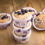 Geschmackvolle Muffin-kleine Kuchen mit Blaubeeren auf einem hölzernen Hintergrund-Stapel des selbst gemachten Muffin-Quadrats lizenzfreie stockbilder