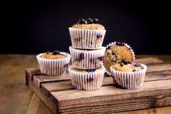 Geschmackvolle Muffin-kleine Kuchen mit Blaubeeren auf einem hölzernen Hintergrund-Stapel von den selbst gemachten Muffins horizo stockfoto