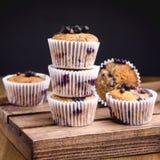 Geschmackvolle Muffin-kleine Kuchen mit Blaubeeren auf einem hölzernen Hintergrund-Stapel von den selbst gemachten Muffins horizo lizenzfreie stockfotos