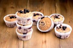 Geschmackvolle Muffin-kleine Kuchen mit Blaubeeren auf einem hölzernen Hintergrund-Stapel von den selbst gemachten Muffins horizo stockfotografie