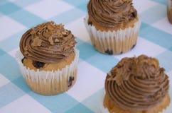 Geschmackvolle Muffins mit der Schokoladencreme verziert mit Zuckersüßigkeiten in einer blauen karierten Tischdecke Stockfotografie