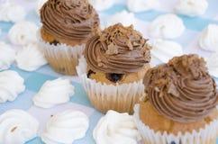 Geschmackvolle Muffins mit der Schokoladencreme verziert mit Zuckersüßigkeiten in einer blauen karierten Tischdecke und in einer  Stockbild