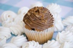 Geschmackvolle Muffins mit der Schokoladencreme verziert mit Zuckersüßigkeiten in einer blauen karierten Tischdecke und in einer  Stockbilder