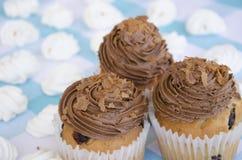 Geschmackvolle Muffins mit der Schokoladencreme verziert mit Zuckersüßigkeiten in einer blauen karierten Tischdecke und in einer  Stockfoto