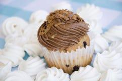 Geschmackvolle Muffins mit der Schokoladencreme verziert mit Zuckersüßigkeiten in einer blauen karierten Tischdecke und in einer  Lizenzfreies Stockbild