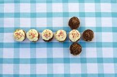 Geschmackvolle Muffins mit der Vanille- und Schokoladencreme verziert mit Zuckersüßigkeit Stockfotografie