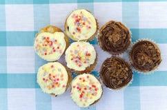 Geschmackvolle Muffins mit der Vanille- und Schokoladencreme verziert mit Zuckersüßigkeit Lizenzfreie Stockfotos