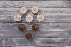 Geschmackvolle Muffins mit der Vanille- und Schokoladencreme verziert mit Zuckersüßigkeit auf einem hölzernen Hintergrund in eine Lizenzfreies Stockfoto