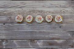 Geschmackvolle Muffins mit der Vanille- und Schokoladencreme verziert mit Zuckersüßigkeit auf einem hölzernen Hintergrund Stockbild