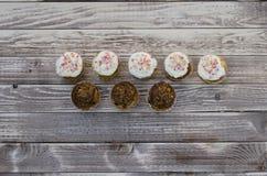 Geschmackvolle Muffins mit der Vanille- und Schokoladencreme verziert mit Zuckersüßigkeit auf einem hölzernen Hintergrund Lizenzfreies Stockfoto