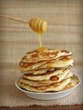 Geschmackvolle Pfannkuchen mit Honig und hölzernem Schöpflöffel Stockfotos