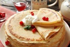 Geschmackvolle Pfannkuchen mit Sahne und Beeren Lizenzfreie Stockfotos