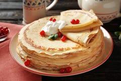 Geschmackvolle Pfannkuchen mit Sahne und Beeren Lizenzfreie Stockfotografie