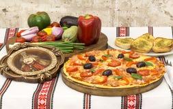 Geschmackvolle Pizza mit Gemüse, Basilikum, Oliven, Tomaten, grüner Paprika auf Schneidebrett, traditionelles buntes der Tischdec Stockfotos