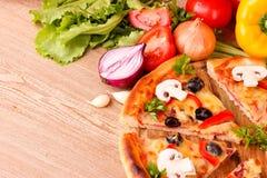 Geschmackvolle Pizza mit Oliven und Gemüse auf einem hölzernen Lizenzfreie Stockfotografie