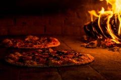 Geschmackvolle Pizza zwei in einem hölzernen brennenden Ofen Stockfoto