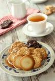 Geschmackvolle Plätzchen auf schöner Platte und Tasse Tee auf hölzernem stockbilder