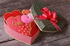 Geschmackvolle Plätzchen im Valentinsgrußherzen formten Kasten auf einem Holztisch lizenzfreie stockbilder