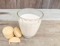 Geschmackvolle Plätzchen und Glas Milch legen auf einen Holztischhintergrund lizenzfreie stockfotografie