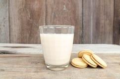 Geschmackvolle Plätzchen und Glas Milch legen auf einen Holztischhintergrund lizenzfreie stockbilder