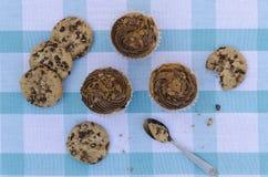 Geschmackvolle Plätzchen und Muffinkuchen mit der Schokoladencreme verziert mit Zuckersüßigkeiten auf einer blauen karierten Tisc Stockfotografie