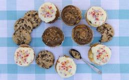 Geschmackvolle Plätzchen und Muffinkuchen mit der Schokoladencreme verziert mit Zuckersüßigkeiten auf einer blauen karierten Tisc Stockbild