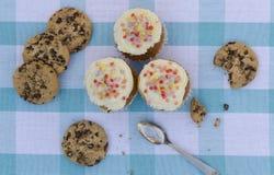 Geschmackvolle Plätzchen und Muffinkuchen mit der Vanillecreme verziert mit Zuckersüßigkeiten auf einem hölzernen Hintergrund Stockfoto