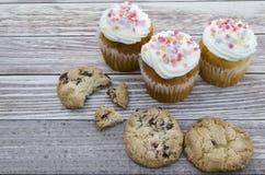 Geschmackvolle Plätzchen und Muffinkuchen mit der Vanillecreme verziert mit Zuckersüßigkeiten auf einem hölzernen Hintergrund Stockfotos