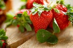 Geschmackvolle rote Erdbeeren auf rustikalem Tabellenabschluß oben Lizenzfreies Stockfoto