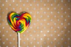 Geschmackvolle runde Süßigkeiten auf hölzernem Stock auf Papierhandwerkshintergrund mit Sternen Kopieren Sie Raum für Text und en Lizenzfreies Stockbild