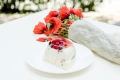 Geschmackvolle süße Fruchttorte und Blumenstrauß von roten Blumen der Mohnblume auf weißer Tabelle Lizenzfreies Stockfoto