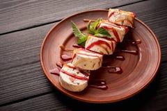 Geschmackvolle Süßspeise, Eiscreme-Vanillearoma in einer Lehmplatte Gedient mit Minze und Belägen Auf schwarzem hölzernem stockfoto
