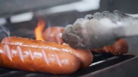 Geschmackvolle saftige W?rste, die ?ber einem Feuer grillen Kochen Sie den Mann, der W?rste auf dem Grill zubereitet W?rfe auf de stock footage