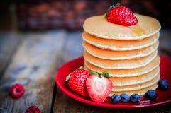 Geschmackvolle selbst gemachte Pfannkuchen mit Erdbeeren, Blaubeeren und Ahorn Stockfoto