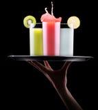 Geschmackvolle Sommerfruchtgetränke mit Spritzen auf Behälter Stockfoto