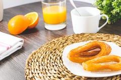 Geschmackvolle spanische churros, Orangensaft, Kaffeefrühstück Orange schnitten Tischplatte mit churros stockbild