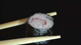 Geschmackvolle Stücke Sushi auf einem schwarzen Stein stock video footage